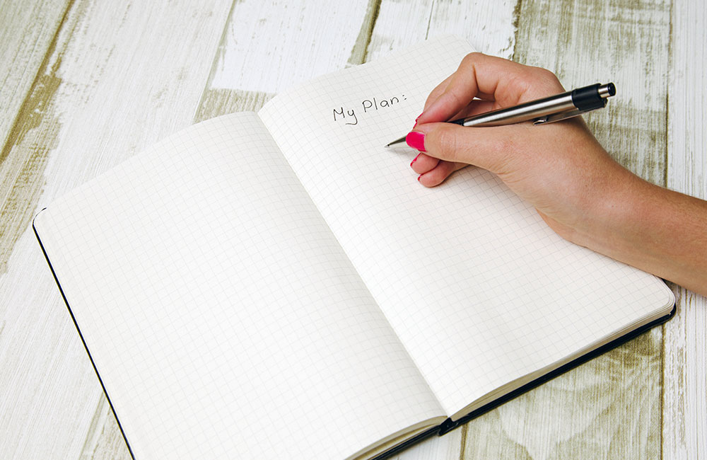 woman making a plan in a notebook